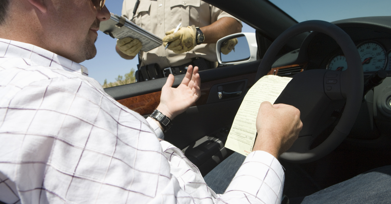 A man sits in his car as he is presented with a speeding ticket from a police officer
