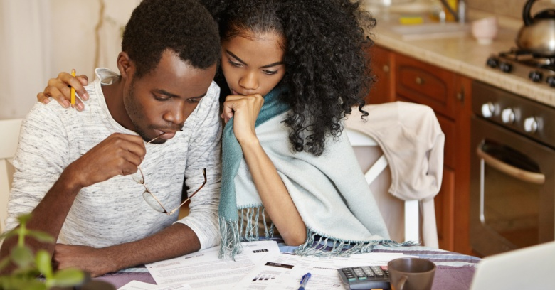 A young couple is reviewing a several financial reports together.