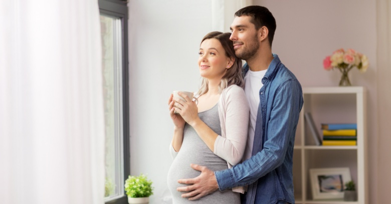 A young man is hugging his pregnant wife who is holding a cup of coffee. They are both looking out the window and enjoying the moment.