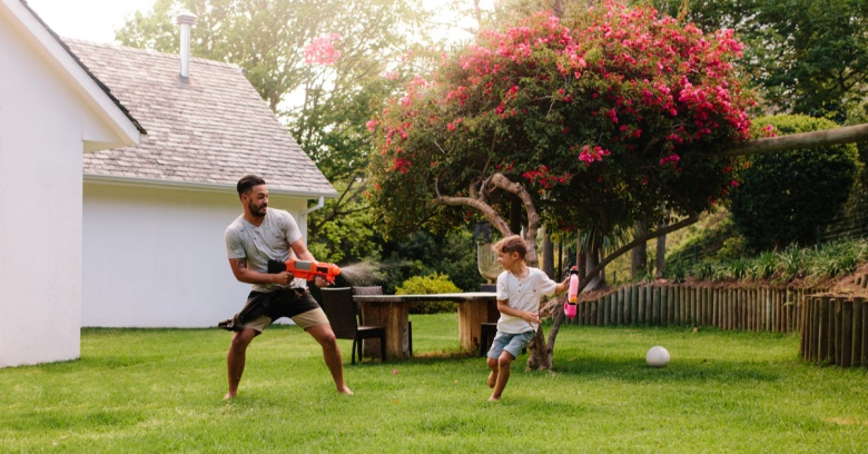 A father and his son play with water guns in the backyard.