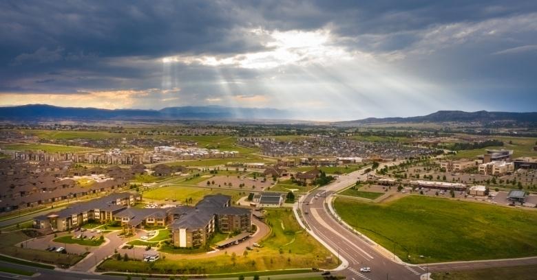 The sun peeks through the storm clouds over Castle Rock, Colorado.