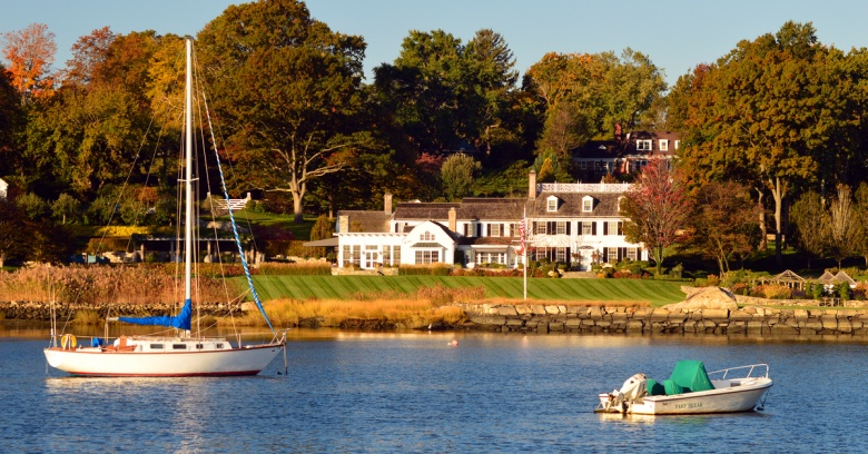 Sailboats pass by a waterfront estate in Greenwich, CT.