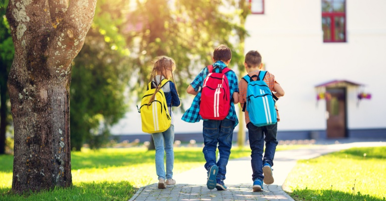 Three kids with backpacks walk home from school.