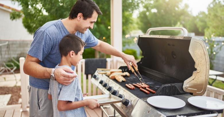 A father shows his son the basics of cooking hot dogs on the grill.