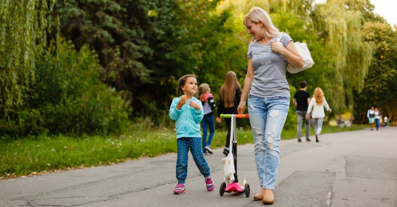 A mother and her daughter walk along a paved trail with a small child's scooter between them.