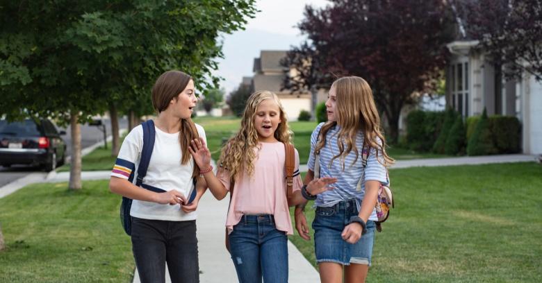 A group of three girls walk down a neighborhood street.