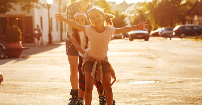 Three sisters rollerblade down the street.