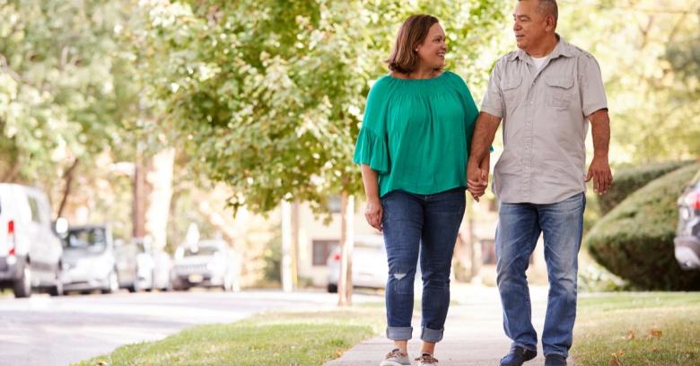 Couple walks down a neighborhood street.