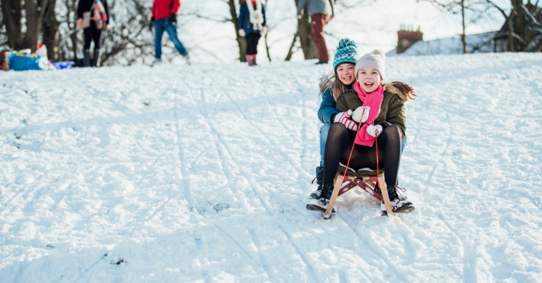 Two girls sled down a snowy hill.