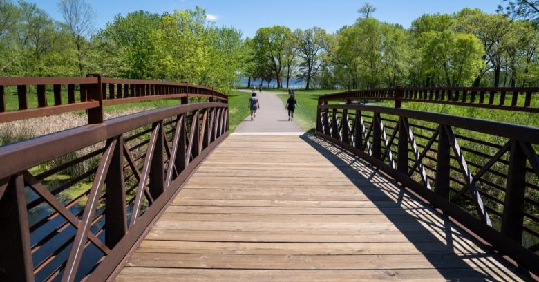People walk near a park footbridge in Plymouth, Minnesota.