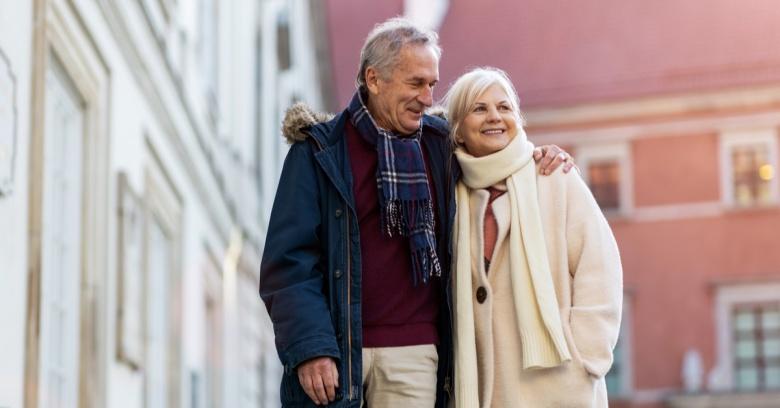 Senior couple walks down a neighborhood street on a cold winter's day.