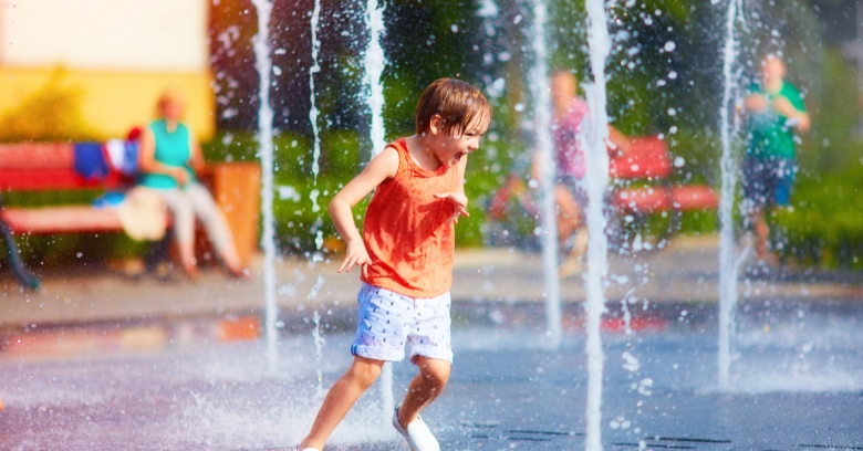 Child has fun playing in a water fountain