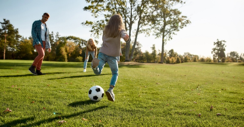 A mother, father and daughter play soccer in a large field.