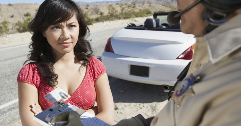 A woman receives a traffic ticket from a police officer.