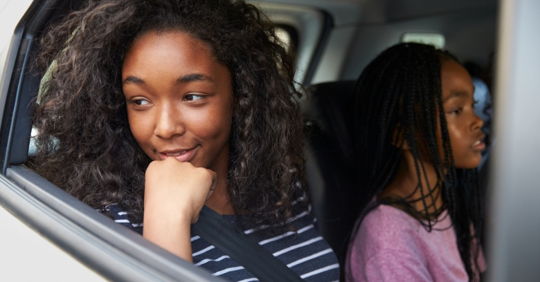 A family with 2 teen daughters travels by car.