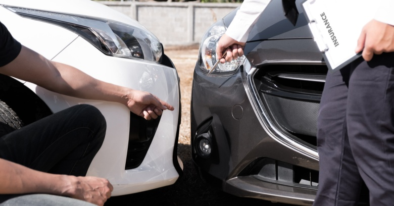A car owner and an insurance adjuster discuss damage to a car.