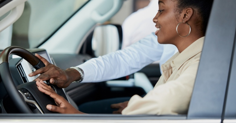 A woman looks at a new car as she considers making a purchase.