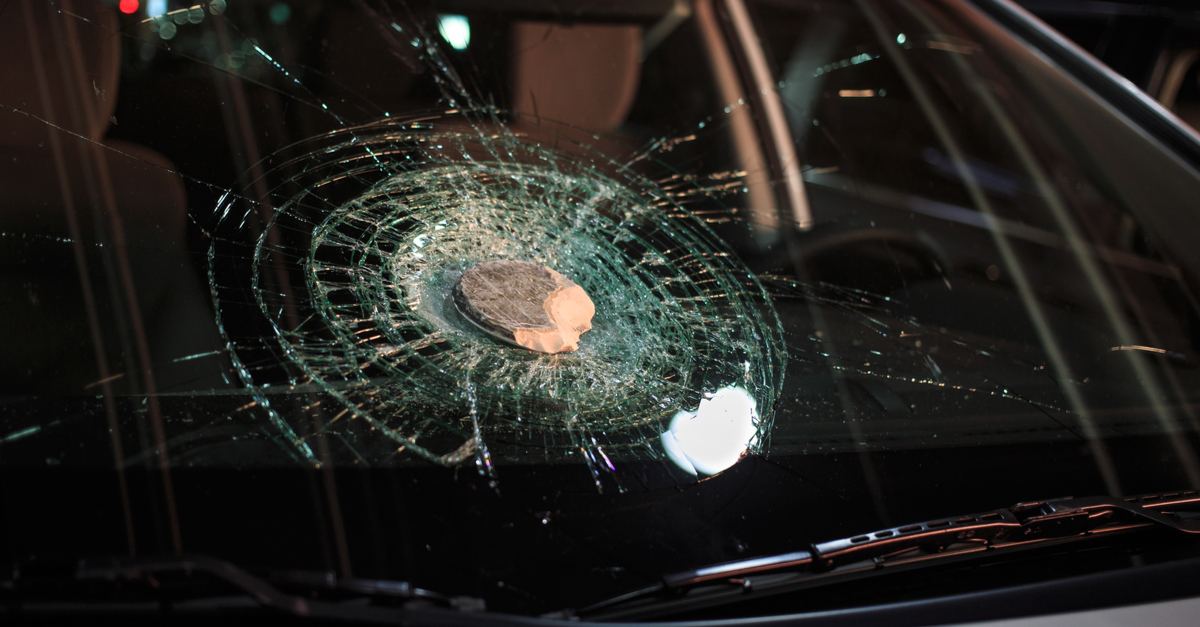 A large rock falls on top of a car's windshield, causing it to crack.