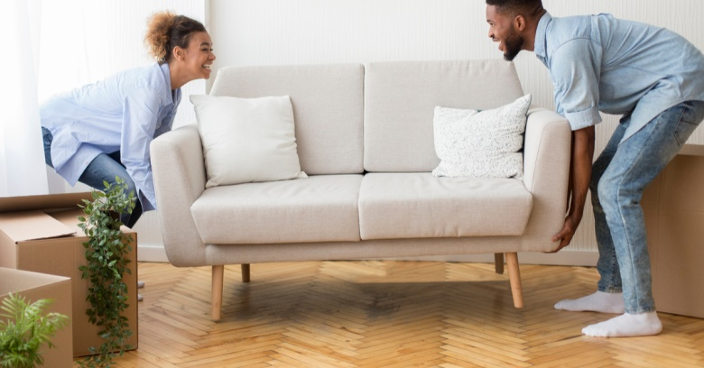 A couple moves a couch into their new home.