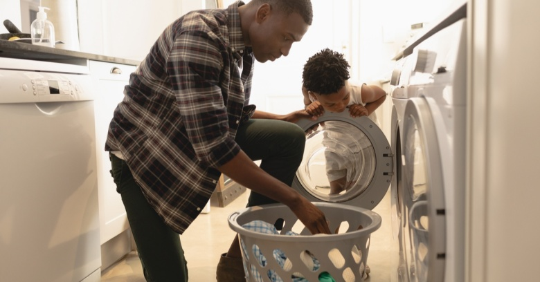 A man takes clothes out of the dryer while his son looks on