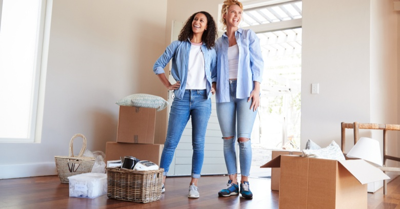 Two women are standing among boxes as they move into their new home.