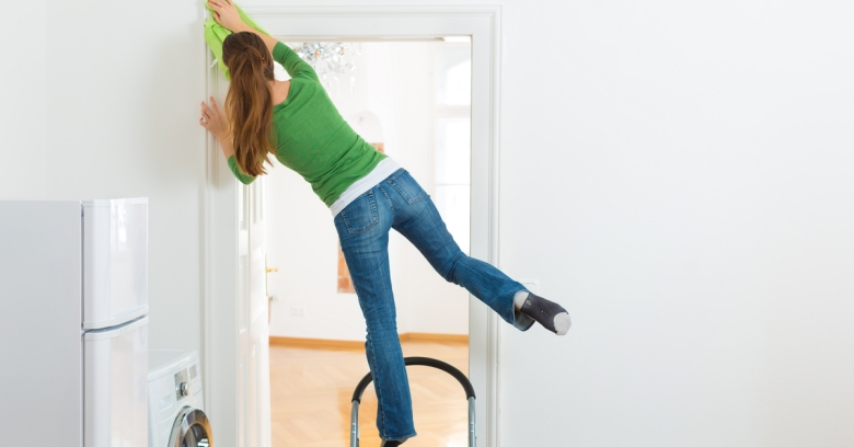 A woman balances precariously on a ladder as she cleans a door
