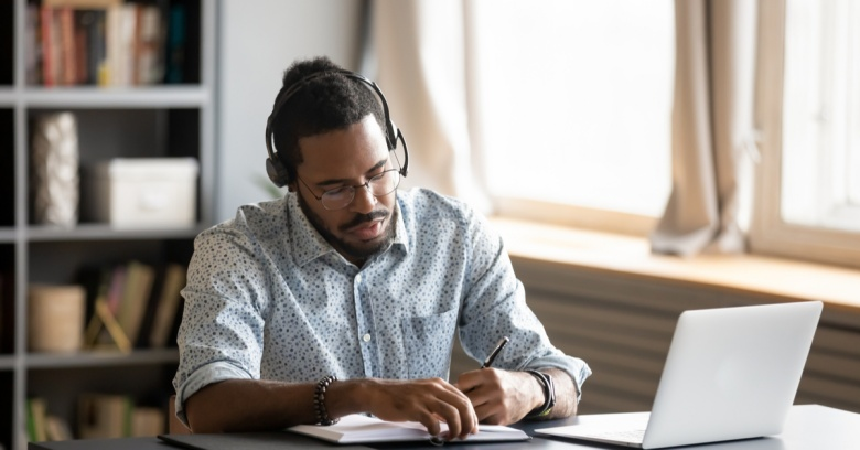 A man works quietly in his home office while he concentrates and wears headphones.
