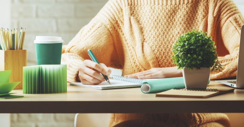 Closeup of a woman working at the desk of her home office. Her desk is tidy and organized and holds a plant, a cup of pencils, a coffee cup, and a notepad.