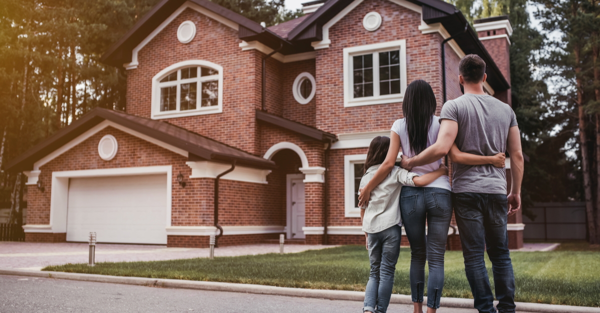 A family is seen from the back admiring their new home in the suburbs.
