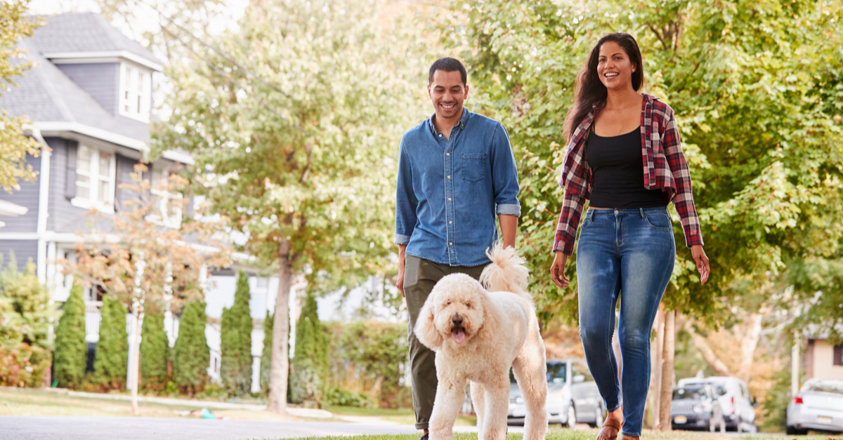 As a result of a lower cost of living, a couple enjoys more time away from work by walking their dog in their suburban neighborhood.