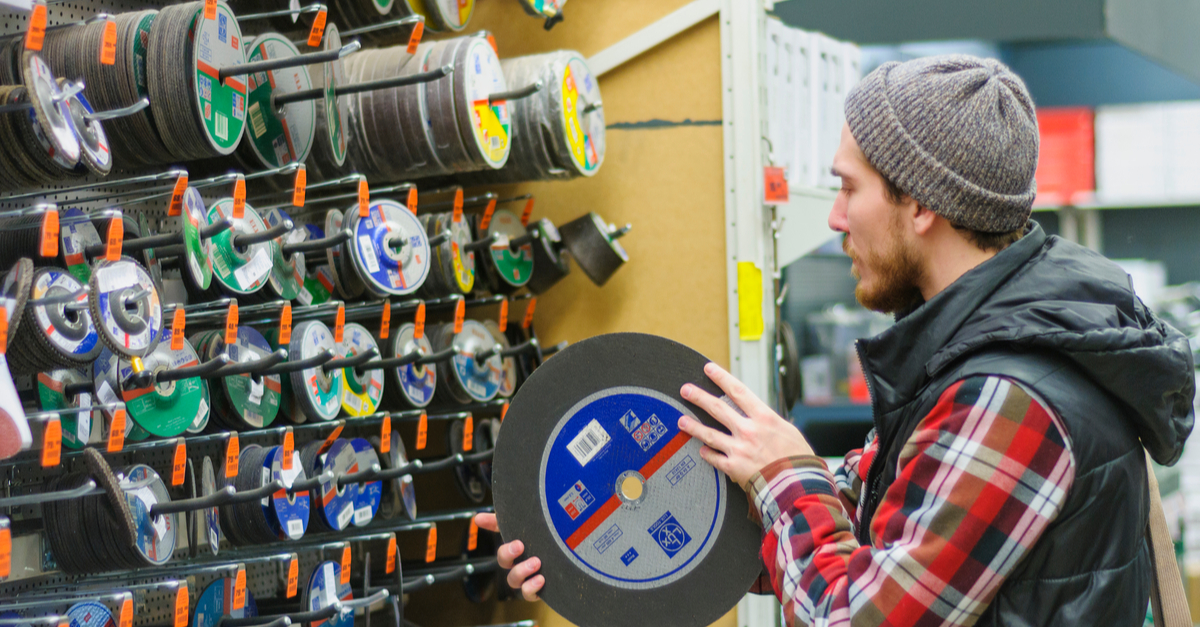 A man dressed in winter clothes prepares his rural home for winter by shopping for tools.