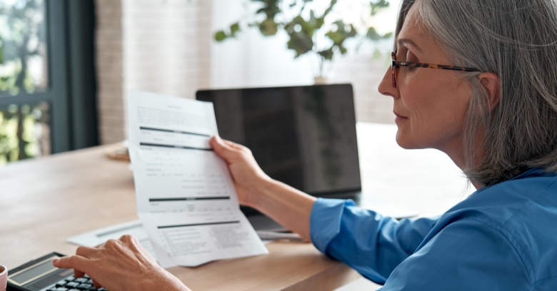 A woman looks at her computer as she determines how much of her tax refund she will add to her retirement account