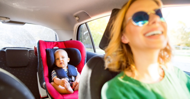 A woman is driving a car with her baby in the backseat. She is smiling because she was able to afford better car insurance after receiving her tax refund