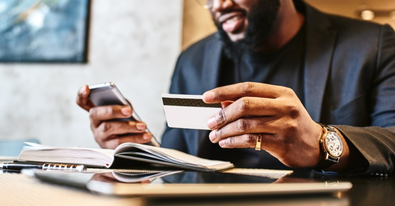 A man looks at his credit card and his phone as he prepares to put his tax refund towards paying down his credit card debt