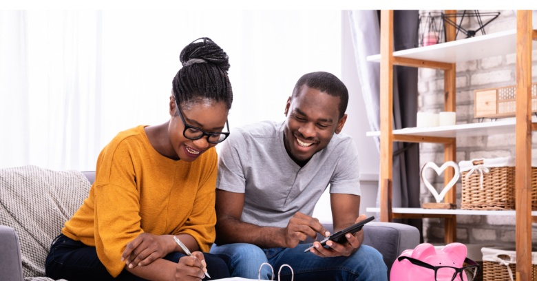 A couple looks at their computer while calculating how much of their tax return they will be able to contribute to their emergency savings