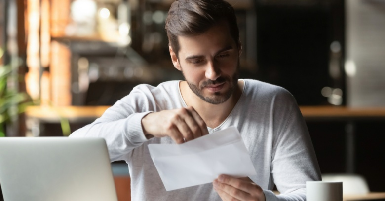 A young man views his student loan invoice as he prepares to use his tax return to make a large payment towards paying off his student loan
