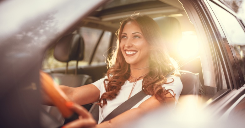 A woman drives with a smile on her face because she has just used her tax refund to pay off her car loan