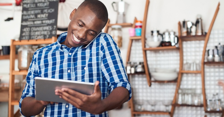 A small business owner smiles while looking at his computer tablet and seeing the amount of money he will be able to use from his tax refund to put toward his business