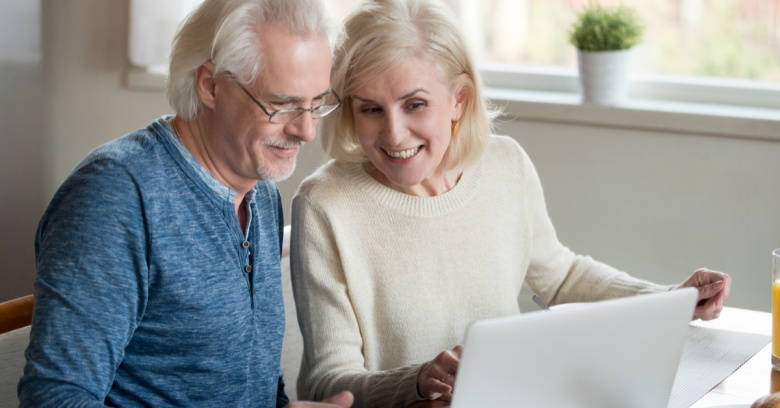 An older couple looks at life insurance policies online to determine which one they should purchase with their tax refund