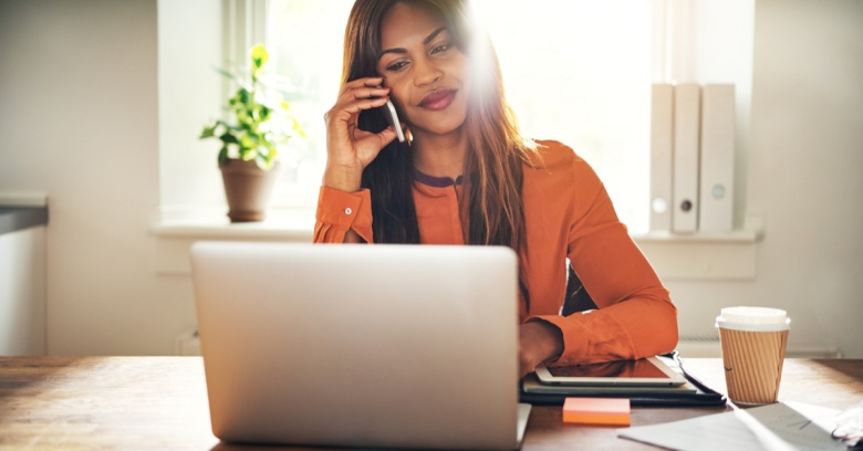 A savvy woman searches for good real estate deals by using her computer and speaking with her real estate agent on the phone