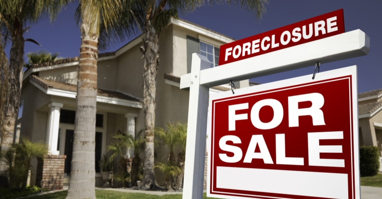 A 'foreclosed' sign is shown in front of a home