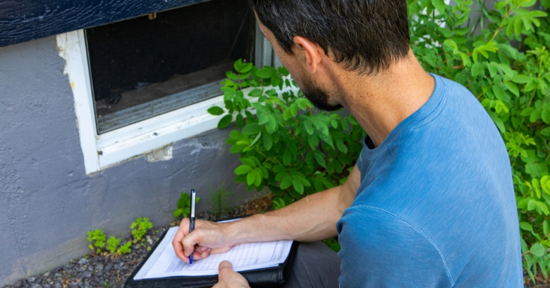 a home inspector takes notes as he thoroughly inspects a home