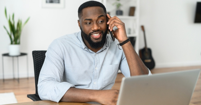 A smiling man speaks with his insurance agent on the phone to make sure his home is properly protected