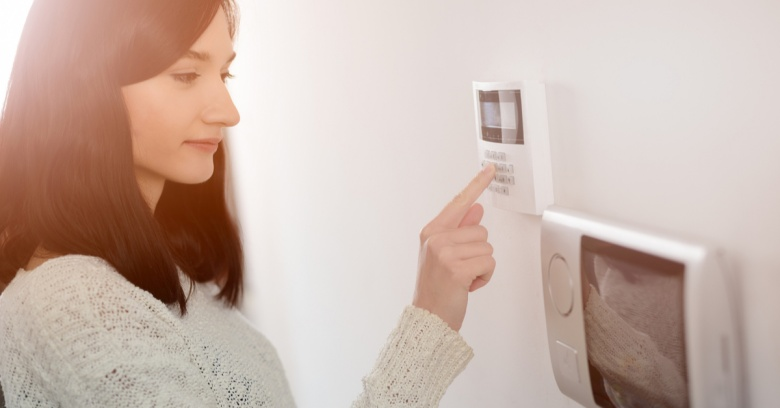 A woman uses the keypad on her newly installed home security system