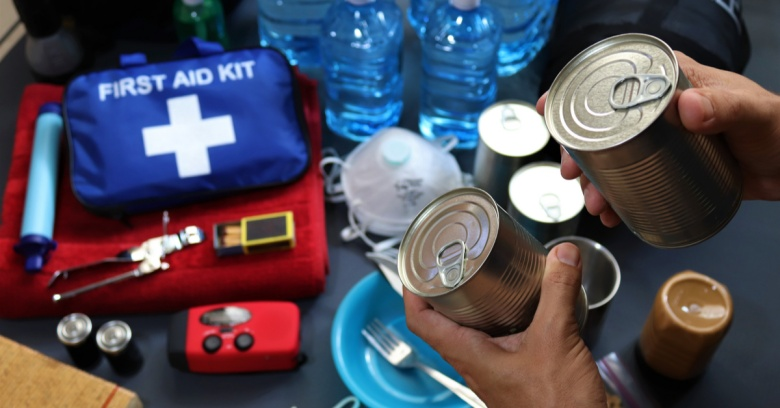A homeowner gathers a flashlight, canned food and other supplies to create an emergency supply kit to be used in the event of a hurricane, flood or other weather event