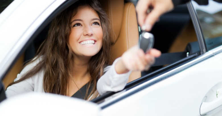 A smiling woman sitting in the driver's seat of a car smiles as keys to her new car are handed to her. She is happy to be building her credit with her auto loan.