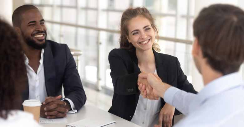 A young woman shakes the hand of a new employee. He will be starting a new job out of college.