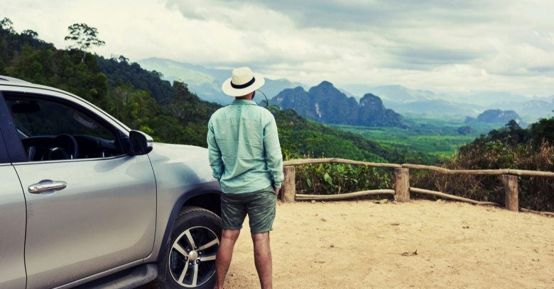 A man on a solo road trip he has budgeted for stands near his car looking out at a canyon and mountains.