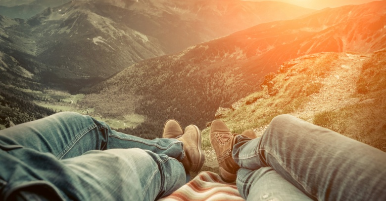 A young couple enjoys a sunset looking over the scenery as they take a break during their frugal road trip.