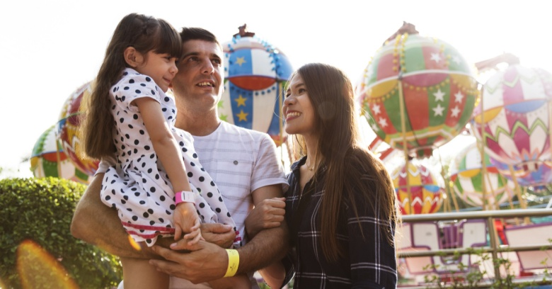 A young family spends time at an amusement park during a splurge road trip they have budgeted for.